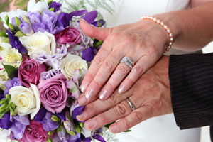 Bride and groom hands with wedding rings & flowers | ©Sherry Clewell Photography